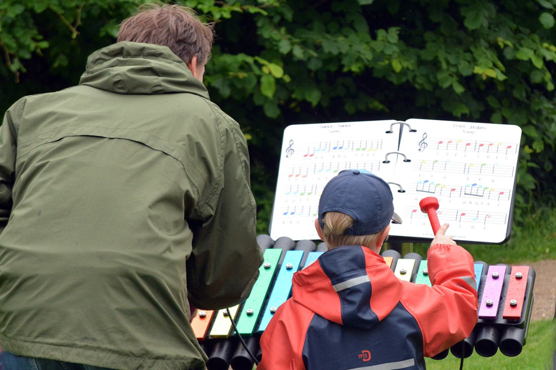 A father and son playing an outdoor xylophone with an outdoor music book