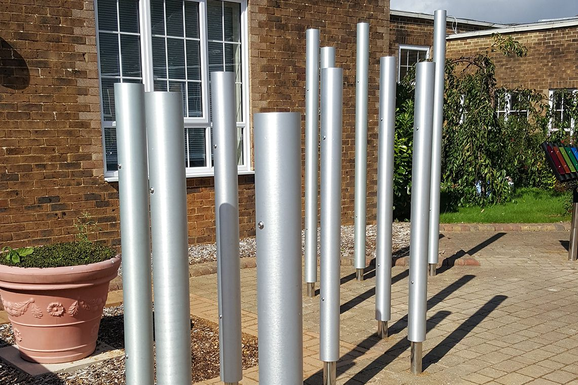 Tall silver chimes installed in a playground