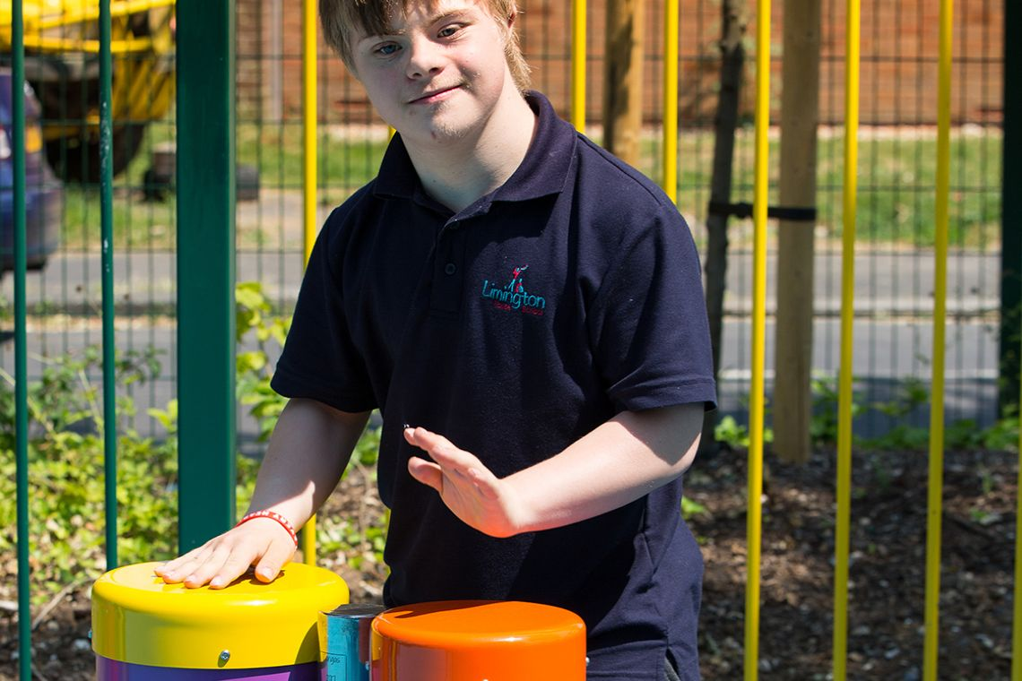 boy with special needs playing colourful outdoor drums in a school playground