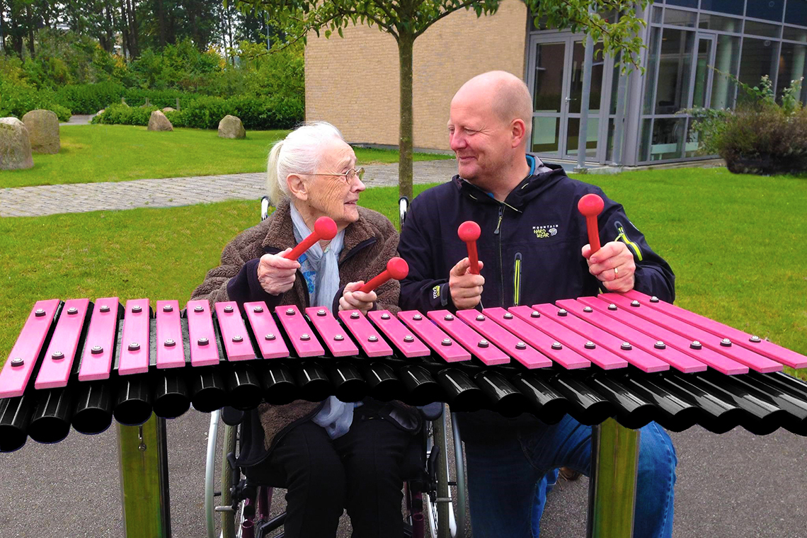 Man kneeling next to an elderly lady in a wheelchair playing an outdoor xylophone