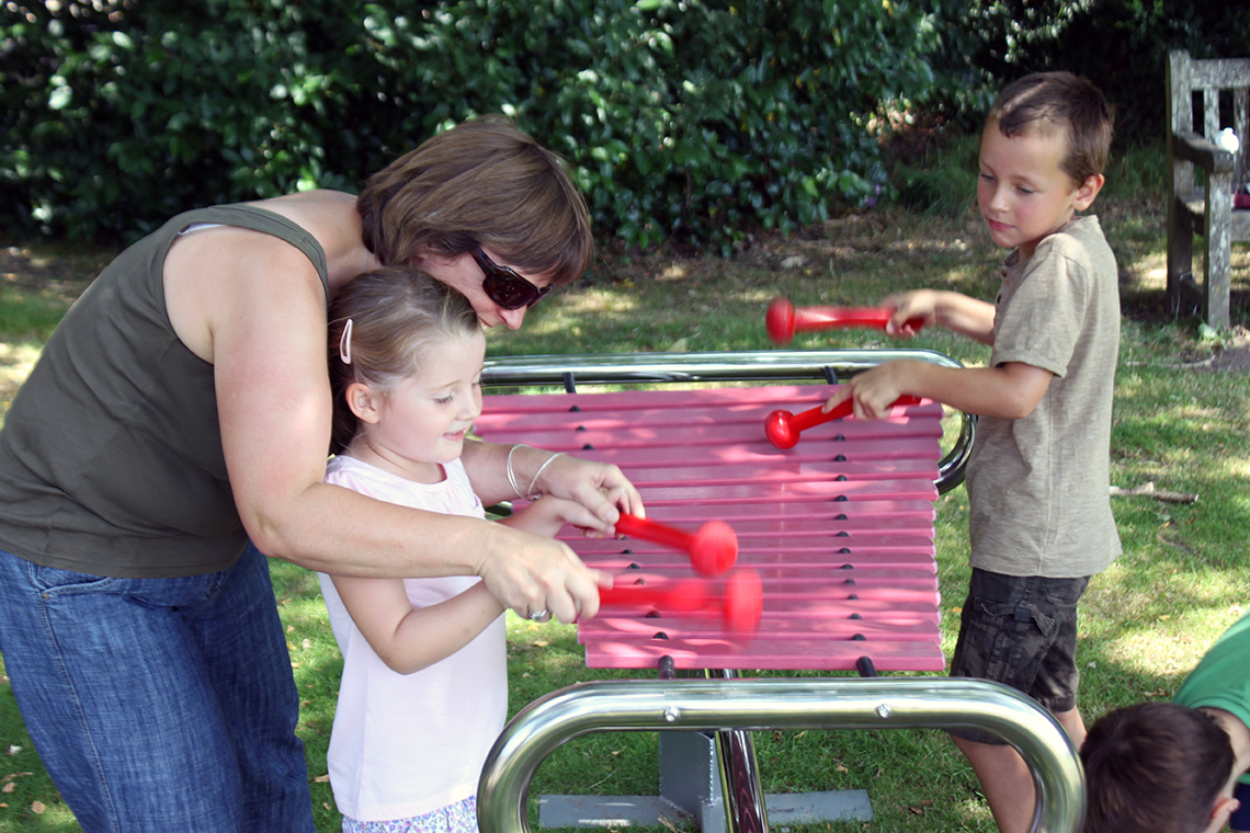 two children and mother playing a large marimba with pink notes in the park