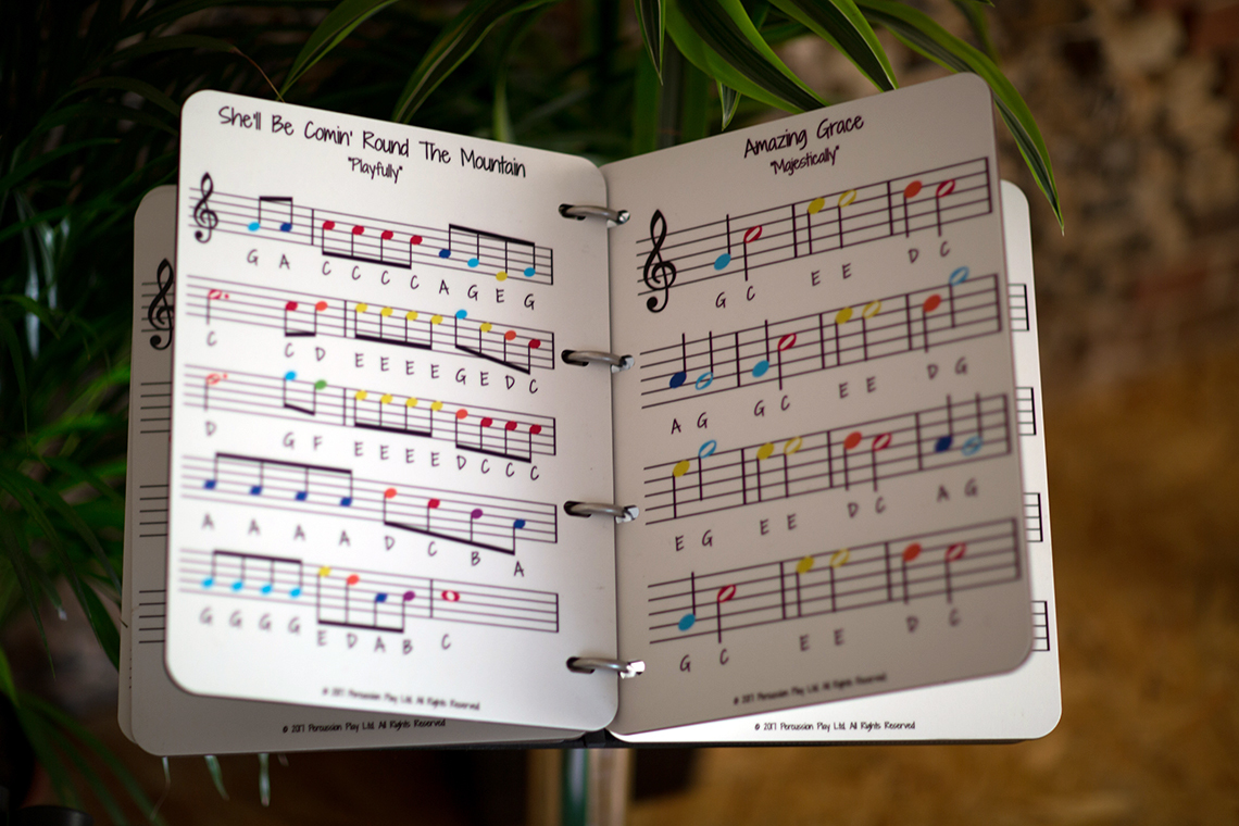 A large music book to accompany an outdoor musical instruments using a rainbow scale