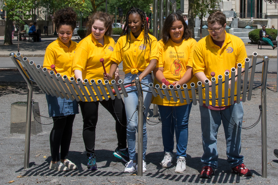 Five Teenagers dressed in yellow t-shirts playing an outdoor musical instrument in Syracuse USA