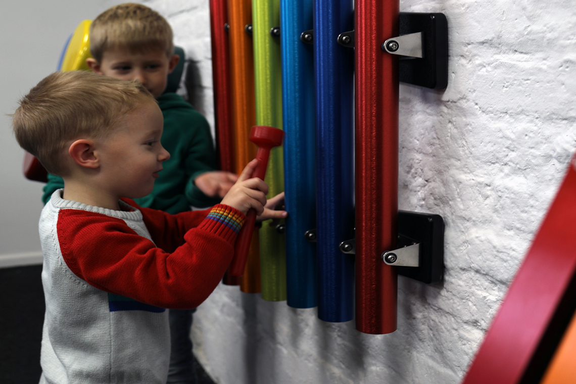 a set of bright rainbow coloured pentatonic chimes for wall mounting in school playgrounds