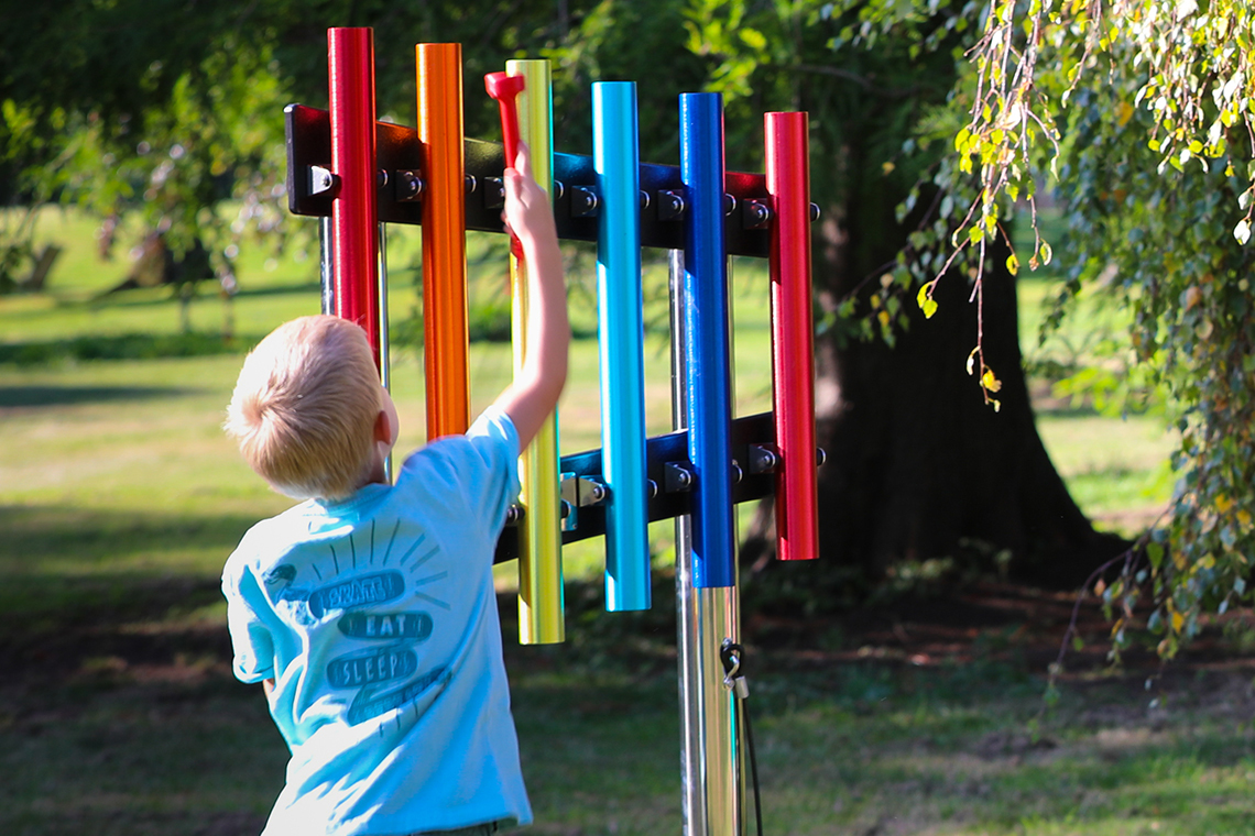 Young boy reaching up and playing a rainbow coloured set of six musical chimes in a school playground