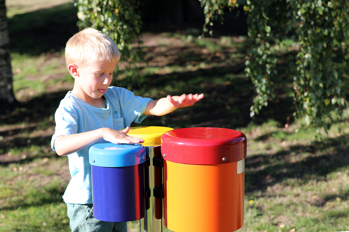 a young boy playing on a set of three colourful outdoor drums in a playground