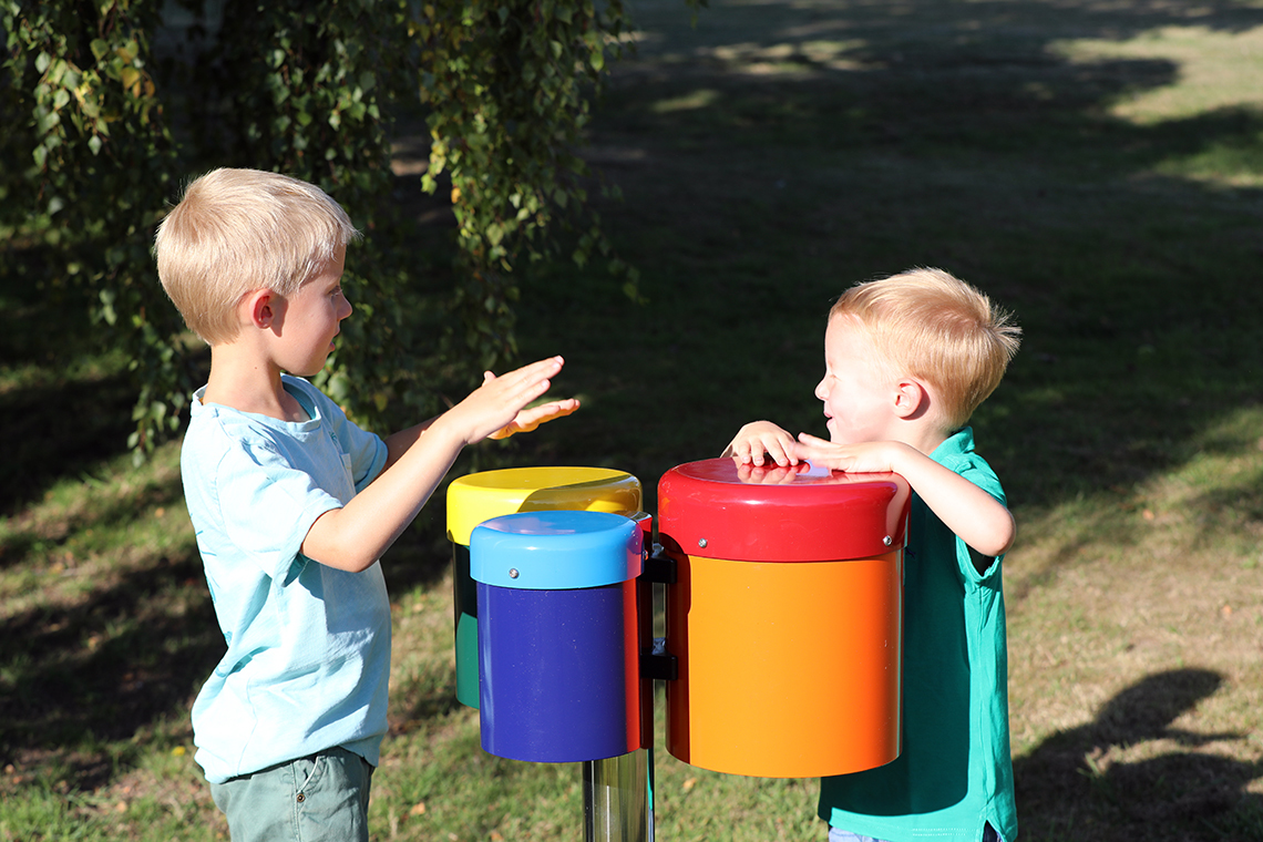 Two young brothers playing on a set of outdoor rainbow coloured drums in a playground
