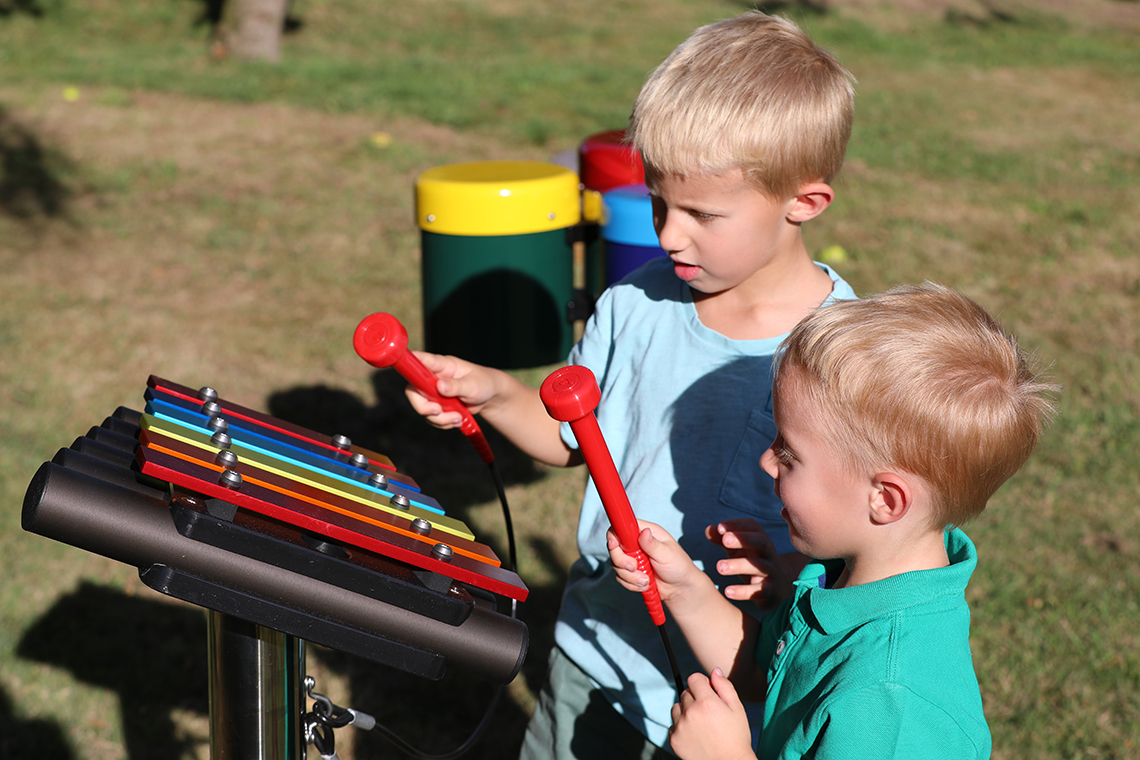 Two young brothers playing on a small rainbow coloured outdoor xylophone in a playground