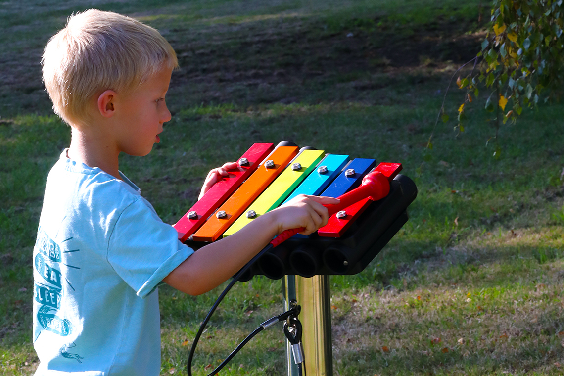 a young boy playing on a small rainbow coloured outdoor xylophone mounted on a stainless steel post in a playground