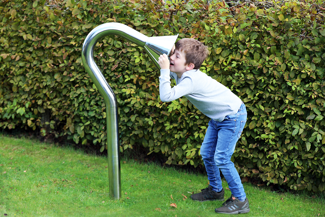 boy speaking into a large stainless steel cone playground talk tube