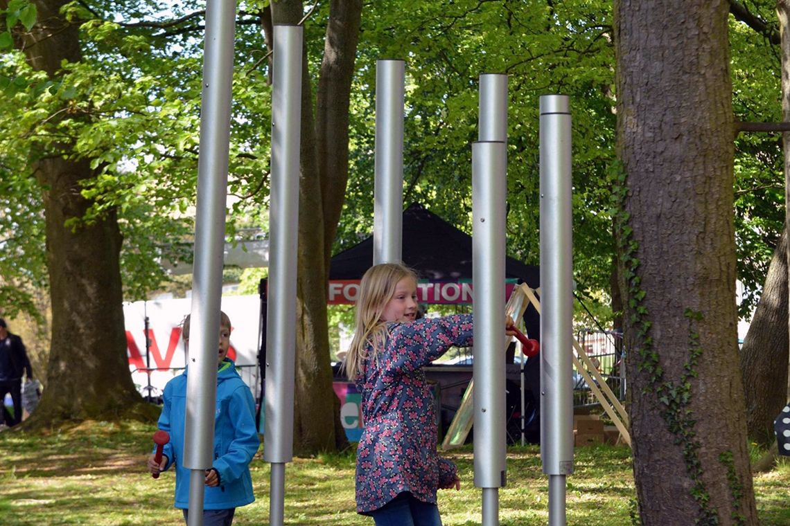 boy and girl playing a large outdoor chimes in a park