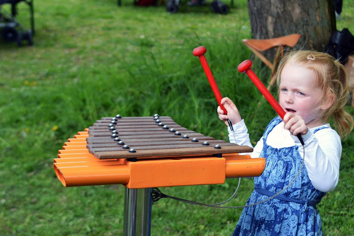 red haired little girl playing an orange outdoor xylophone in a park