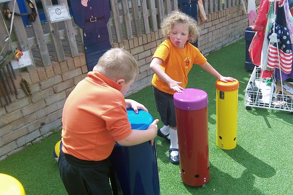 boy and girl with special needs playing colourful outdoor drums in a school playground